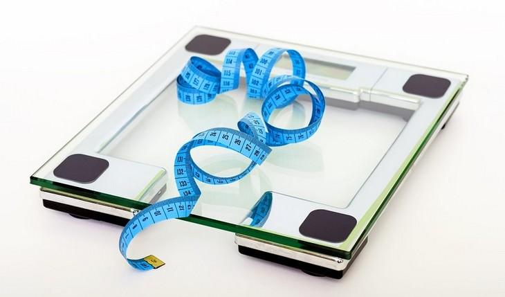 סכנות בריאותיות של שעות שינה מרובות: משקל ביתי ועליו סרט מדידה