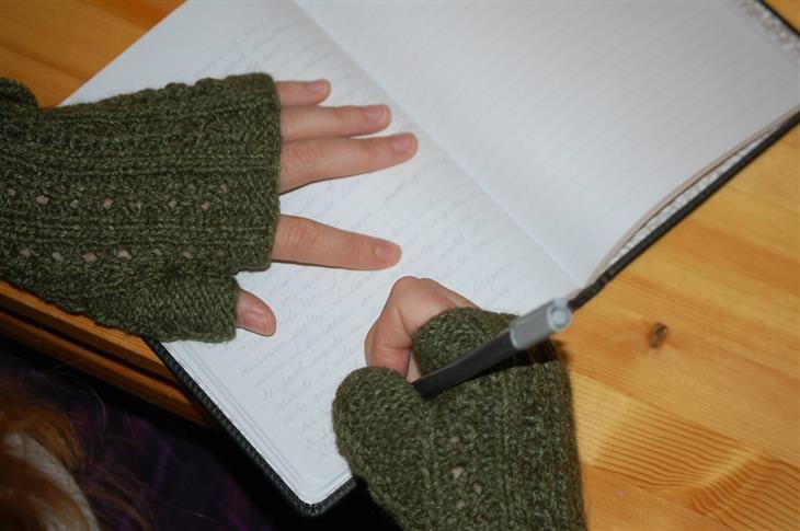 דרכים שבהן רופאים ואחיות נמנעים ממחלות: ידיים של אישה לבושה בסוודר שכותבת במחברת