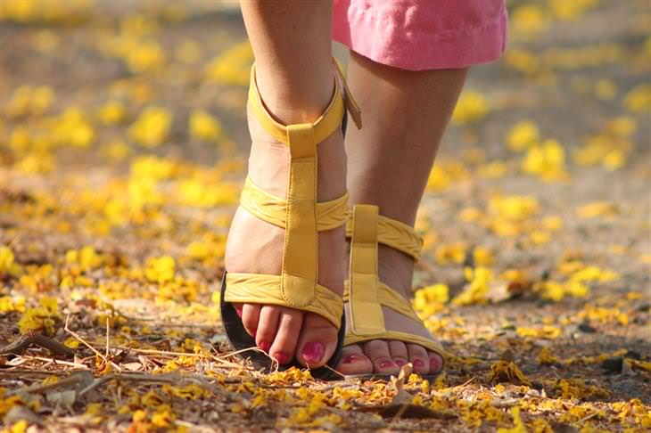 דרכים שבהן רופאים ואחיות נמנעים ממחלות: רגליים של אישה בסנדלים הולכות על אדמה שמכוסה בשלכת פרחונית