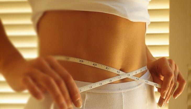 אישה כורכת סרט מדידה על הבטן שלה
