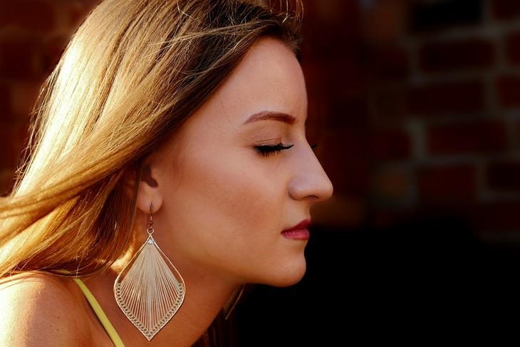 יתרונות בריאותיים של מנדרינות: פרופיל של אישה עם פנים חלקות עוצמת את עיניה