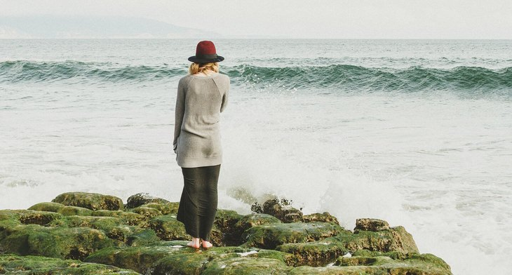 עובדות על החיים: אישה עומדת על סלעים מול ים