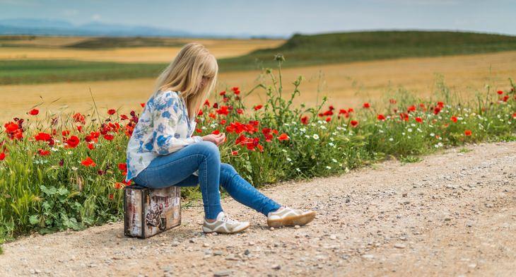 עובדות על החיים: אישה יושבת על מזוודה לצד שדה פרחים אדומים
