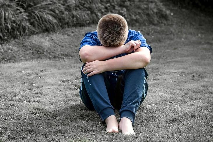 ילד יושב על חול וראשו בתוך ידיו