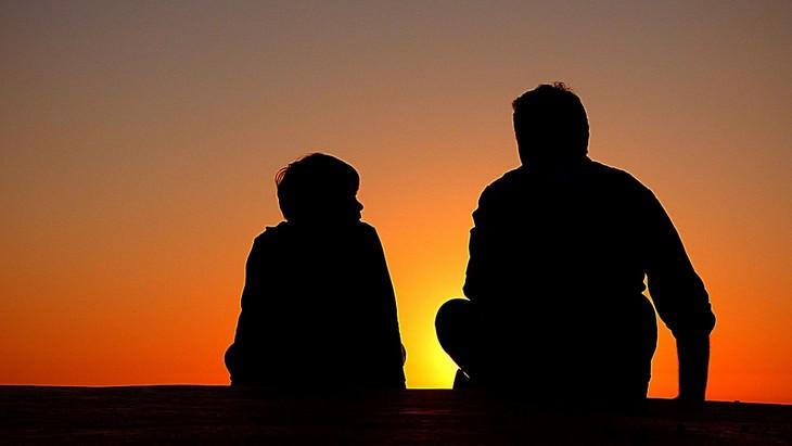 צללית של אב יושב לצד בנו מול השקיעה