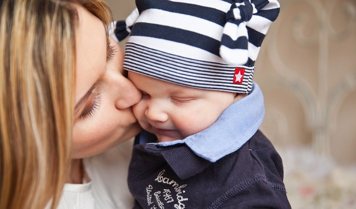אמא מנשקת את תינוקה על הלחי