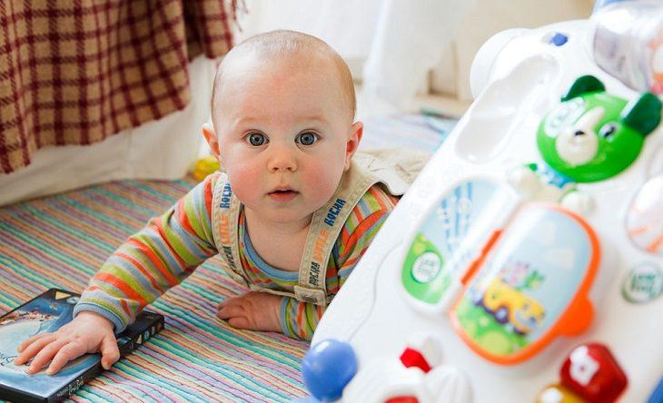 תינוק בחדר צעצועים אוחז בקופסא