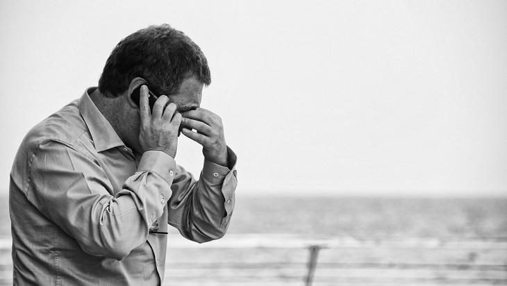 איש לחוץ מניח את ידו על עיניו בזמן שהוא מדבר בטלפון