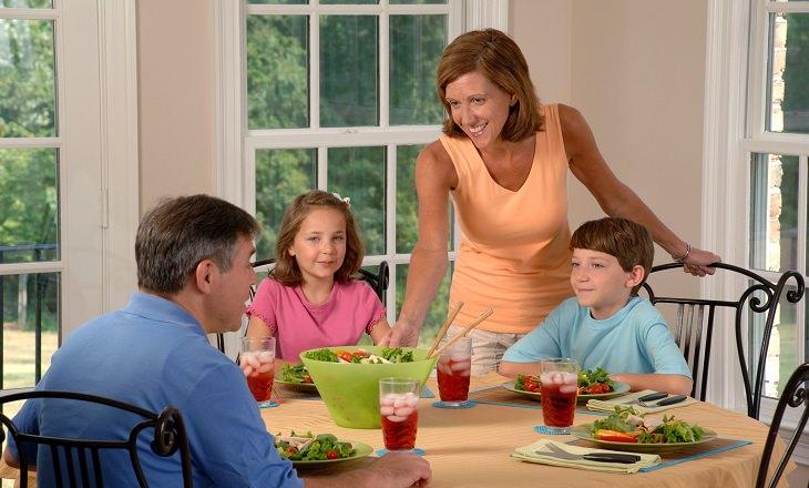 8 סימנים למחסור בסידן: משפחה אוכלת ארוחה ביחד