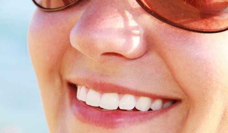 8 סימנים למחסור בסידן: אישה מחייכת