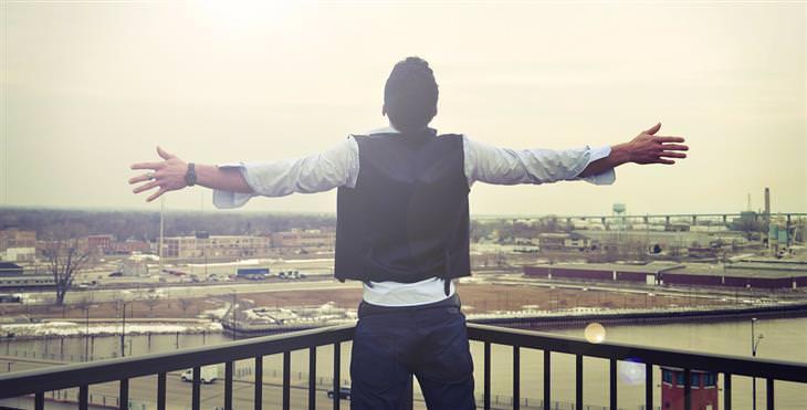 איש פותח את ידיו לצדדים מול נוף עירוני