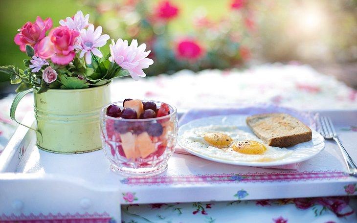 שולחן ערוך בחצר ועליו ארוחת בוקר הכוללת ביצת עין וכוס עם סלט פירות