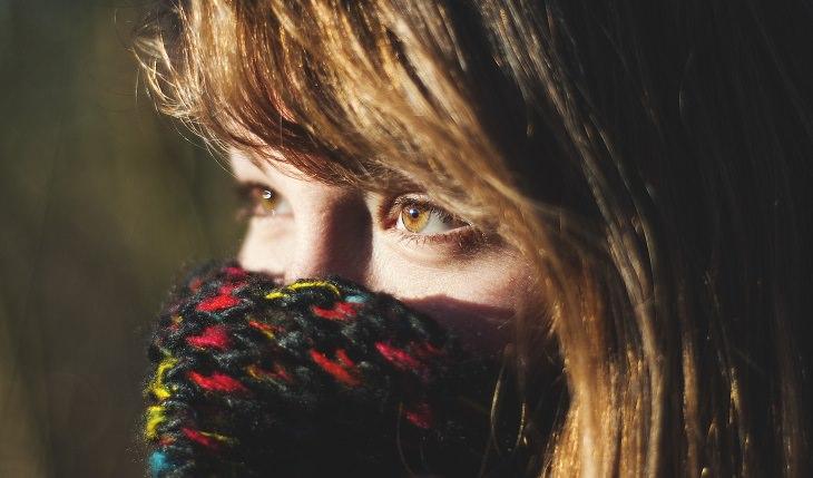 אישה מכסה את הפה עם השרוול של הסוודר