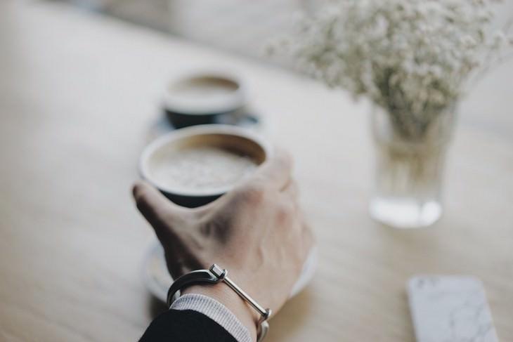 פעולות לשיפור התפקוד המוחי: יד של גבר אוחזת בכוס קפה