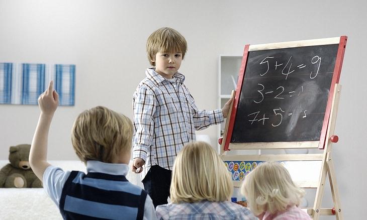 שיטה לדיבור עם ילדים באופן שעוזר להם להצליח בחיים: ילד עומד על יד לוח מול קבוצת ילדים