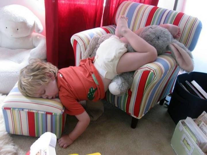 ילד ישן על ספה קטנה כשראשו על ההדום