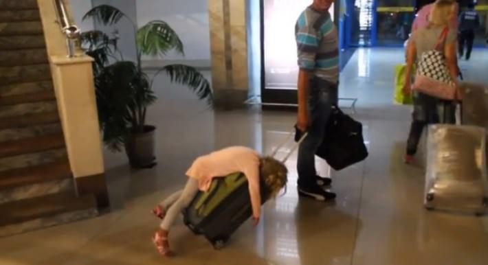ילדה ישנה על מזוודה בנמל תעופה