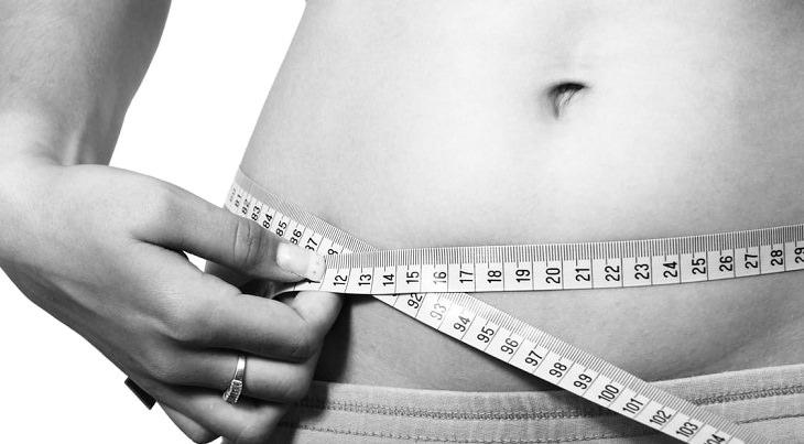 יתרונות ומתכוני קישואים: אישה מודדת את היקף הבטן