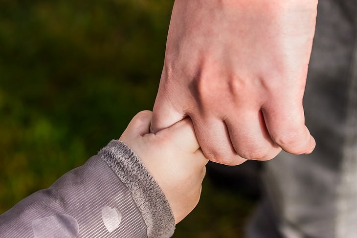 יד של גבר אוחזת בידו של ילד