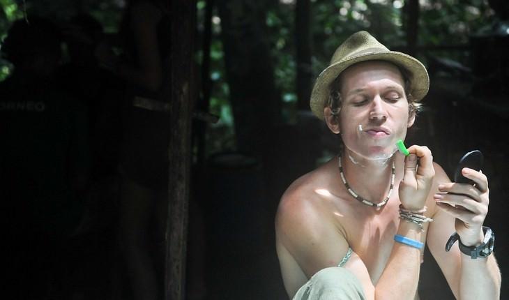 איש ללא חולצה מגלח את פניו בטבע