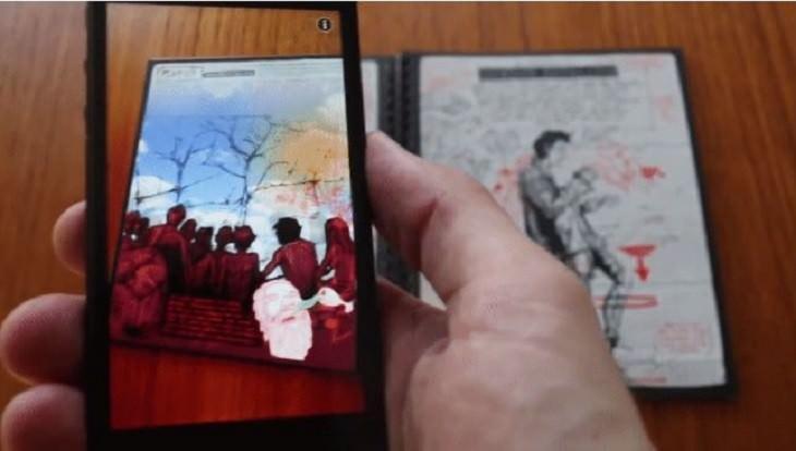 יד של גבר מחזיקה סמארטפון מעל ספר קומיקס