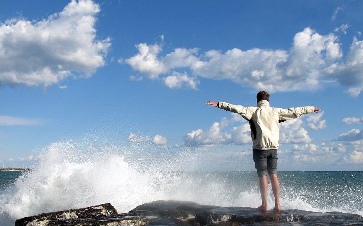 אדם עומד מול הים ומרים את ידיו באוויר