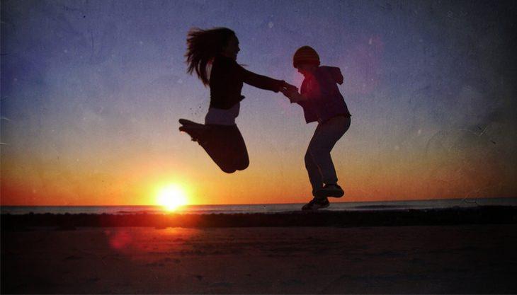 צלליות של גבר ואישה קופצים בחוף הים מול השמש השוקעת