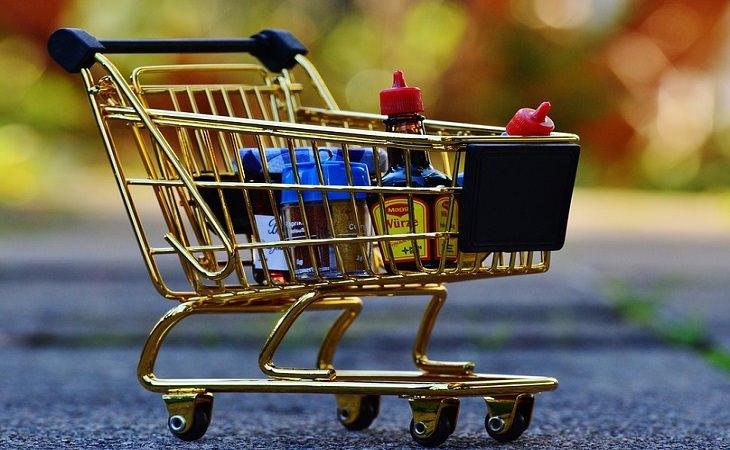 עגלת קניות מוזהבת עם מוצרים שונים בתוכה