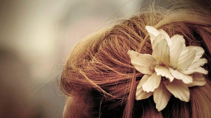 שיער של אישה עם פרח שמקשט אותו