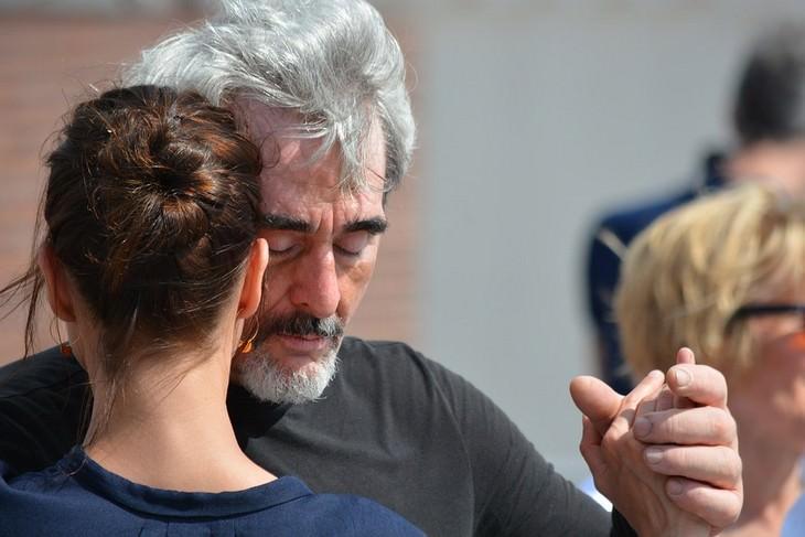 גבר מבוגר עם עיניים עצומות רוקד עם בחורה