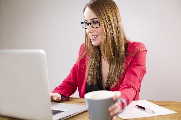 אישה מחייכת מול מחשב נייד
