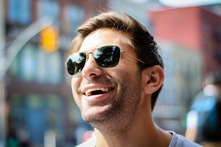 אדם עם משקפי שמש מחייך חיוך רחב