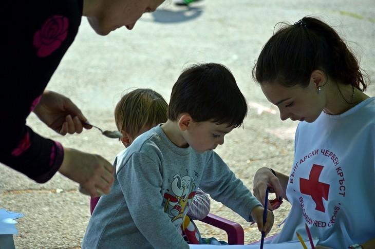 ילד קטן מצייר ליד נערה עם חולצה של מגן דויד אדום