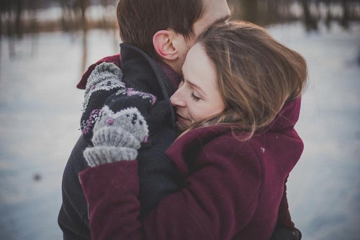 אישה מחבקת את בן זוגה בשלג