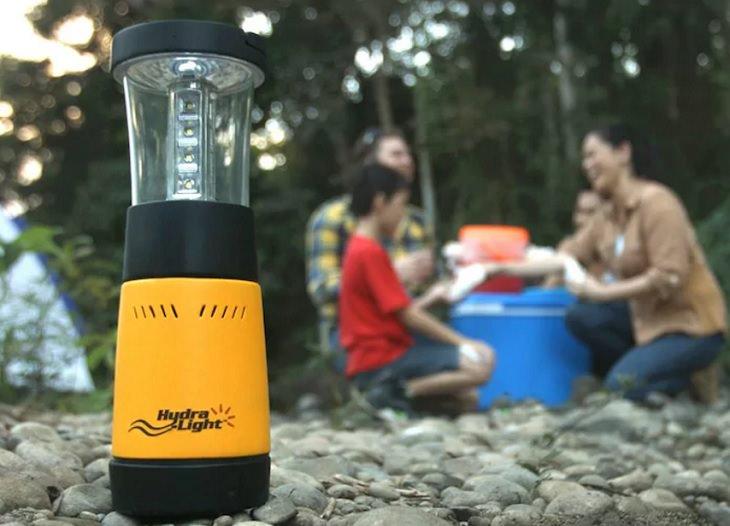מנורה ניידת ליד מטיילים הסועדים בטבע