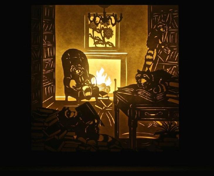 דביבונים יושבים על כיסאות ליד אח בוערת וקוראים ספר