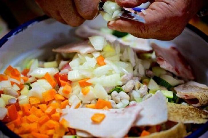 ידיים חותכות את מרכיבי המרק לתוך קערה שמלאה במרכיבים