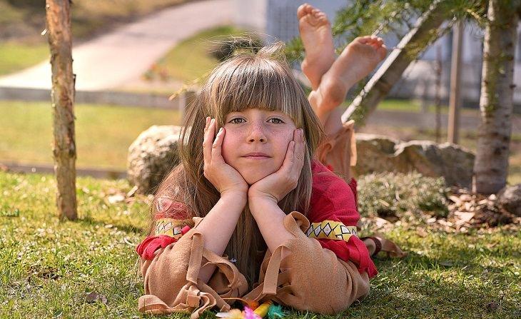 ילדה שוכבת על דשא