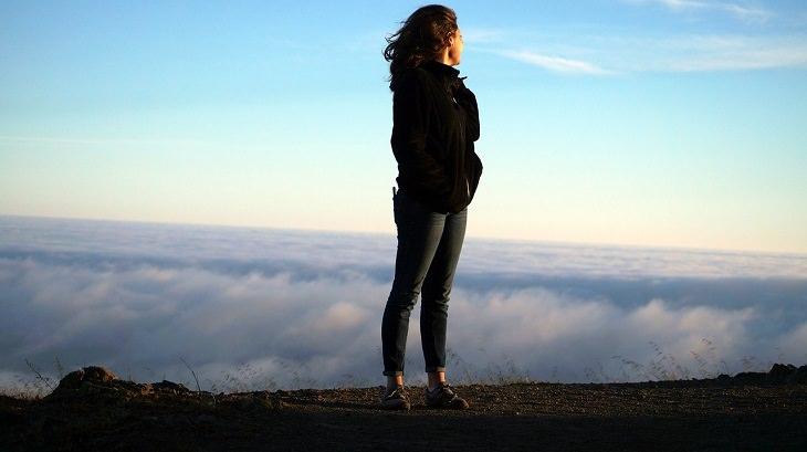אישה ניצבת בראש גבעה