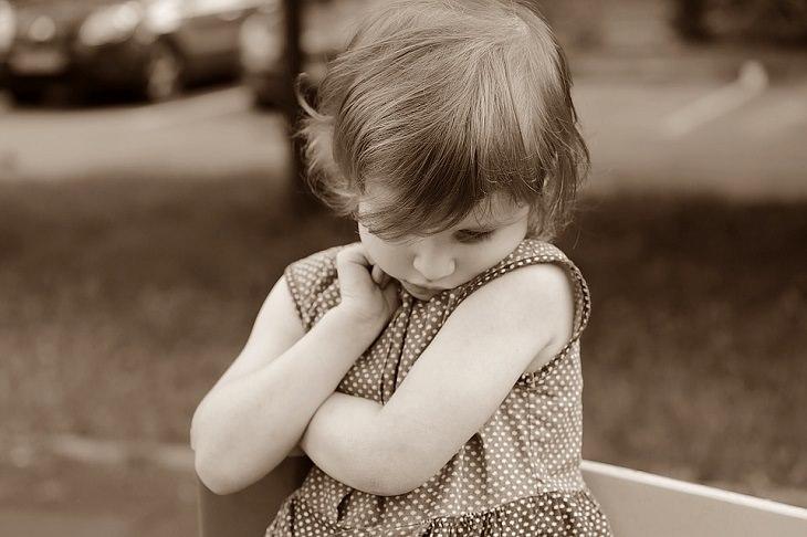 ילדה משלבת ידיים במבוכה ומביטה  מטה
