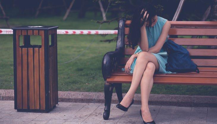 אישה מצוברחת יושבת על ספסל ומחזיקה את ראשה בידה