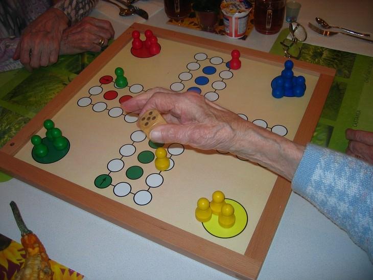 יד של אישה מבוגרת מטילה קובייה על לוח משחקים