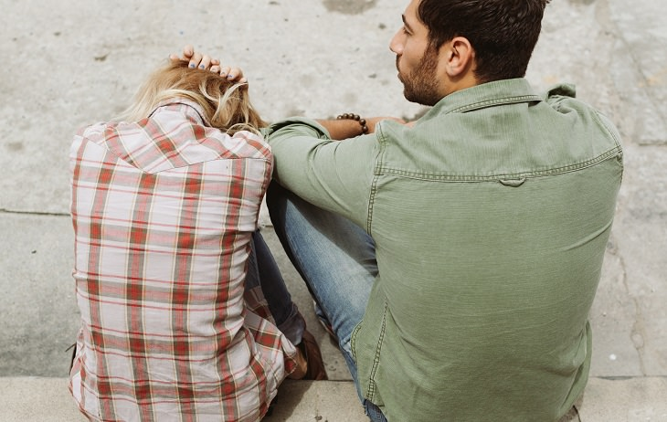 זוג יושב על מדרגה ברחוב ומתווכח