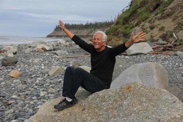 אדם יושב על סלע, פורש ידיים ומחייך