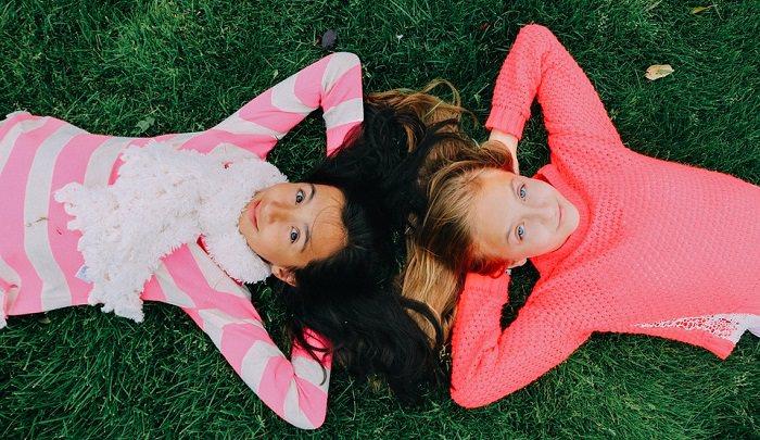 """לגדל ילד חברותי"""" שתי ילדות שוכבות על הדשא"""