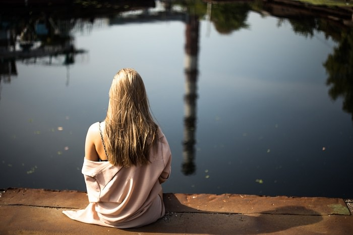 איך לפתח חוסן נפשי: אישה יושבת מול אגם