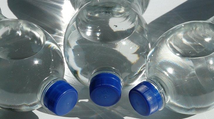 היתרונות הבריאותיים של שתיית מים: 3 בקבוקי מים סגורים ושוכבים