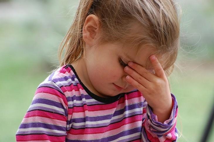 משפטים שהורים לא צריכים להגיד: ילדה מרכינה ראש ואוחזת אותו עם כף ידה