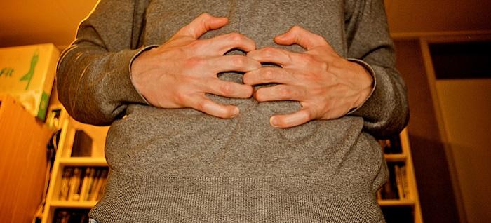 יתרונות הבריאותיים של דג סלמון: אדם תופס את הבטן שלו ולוחץ בשתי כפות ידיו