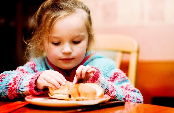 טיפים להורים להרגלי אכילה נכונים לילדים: ילדה יושבת ליד שולחן ובוצעת לחמנייה